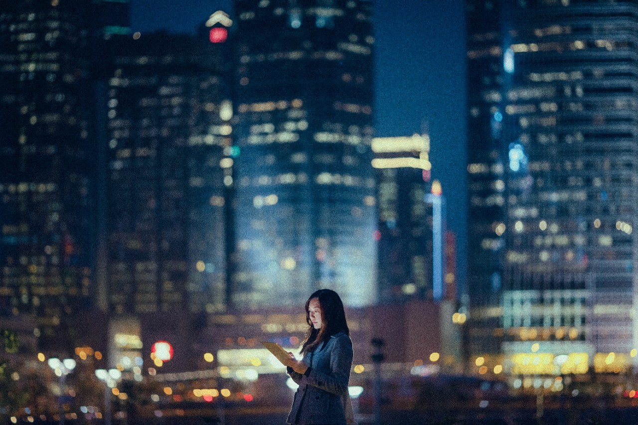 Woman in office at night using digital tablet, standing against illuminated highrise corporate buildings, device, individual, city